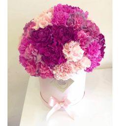 Caja cilíndrica rosada con claveles lila rosado, morado y fucsia